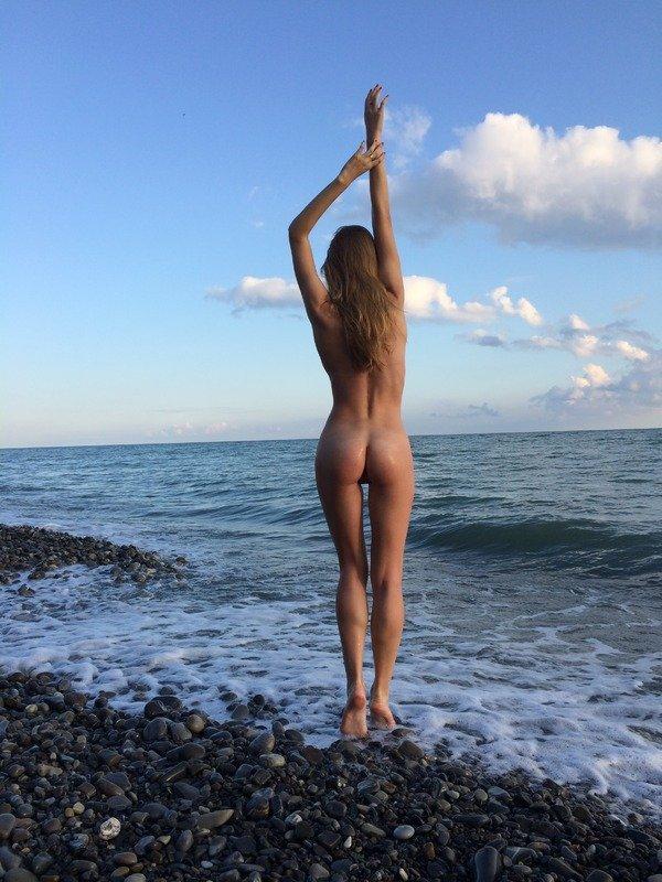 Голая девушка возле моря.